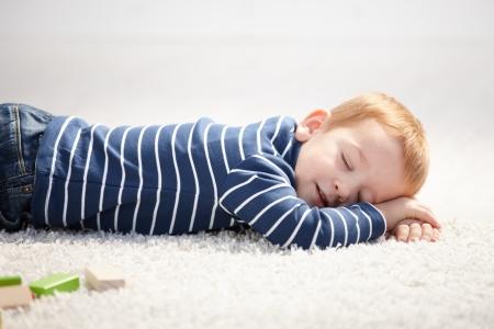 Cute 3 year old boy falling asleep on floor at home.
