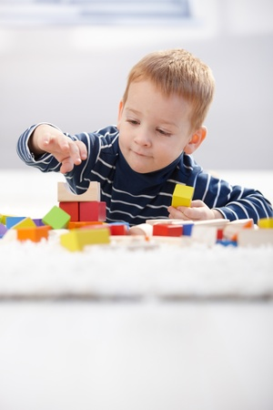 Cute little kid playing on floor with building cubes at home.