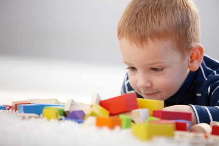 Foto de Adorable ginger-haired little boy playing with cubes, smiling. - Imagen libre de derechos