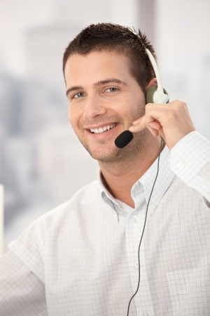 Portrait of happy customer service operator working in bright office.