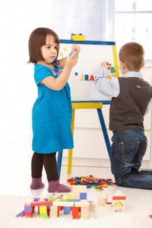 Children playing with magnetic drawing board and alphabet.