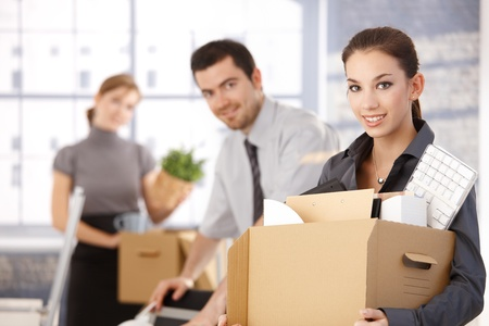 Happy team of businesspeople moving office, packing boxes, smiling.