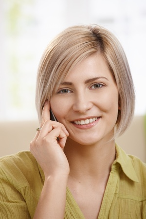 Portrait of attractive young woman speaking on mobile phone at home, smiling at camera. Copyspace on left.
