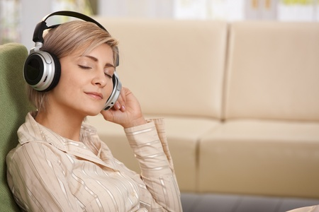 Portrait of smiling woman sitting with eyes closed listening to music on headset.