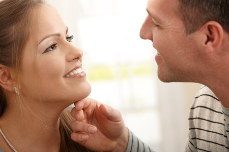 Loving couple smiling at each other, man stroking woman's neck.