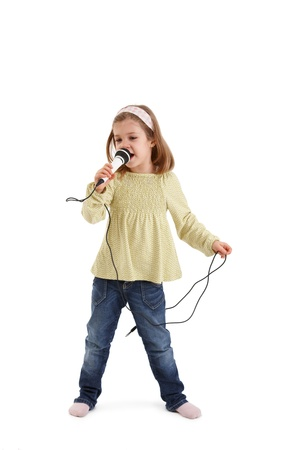 Cute little girl playing with microphone, singing.