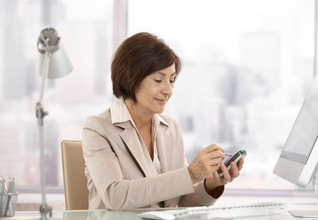Mature female executive using smartphone in office, smiling.
