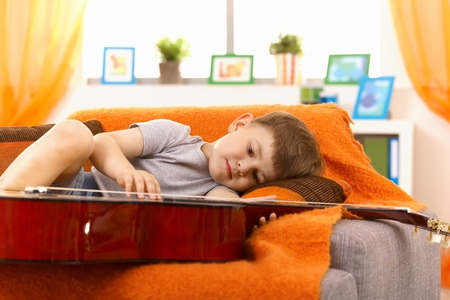Little boy examining guitar while lying on sofa, concentrating.