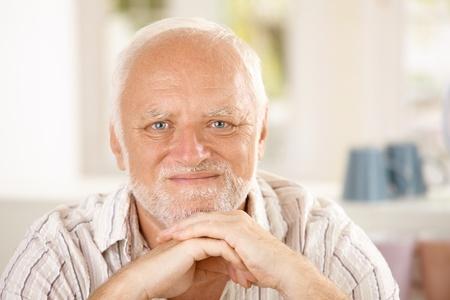 Closeup portrait of content senior man looking at camera.