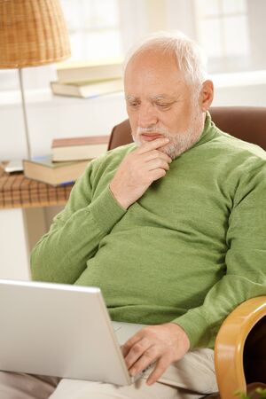 Senior man sitting at home, looking at screen of laptop computer, thinking.