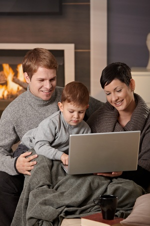Happy family sitting on couch at home in winter, using laptop computer, smiling.