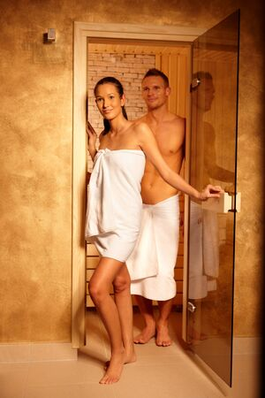 Photo pour Couple standing at sauna door, smiling after relaxing in steam, leaving. - image libre de droit