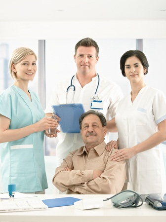 Portrait of senior patient sitting surrounded with medical crew, looking at camera, smiling.