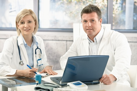Portrait of medical doctors working together in office.