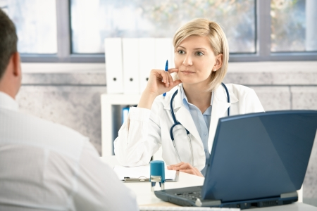 Doctor listening to patient with concentration, sitting at desk in office.