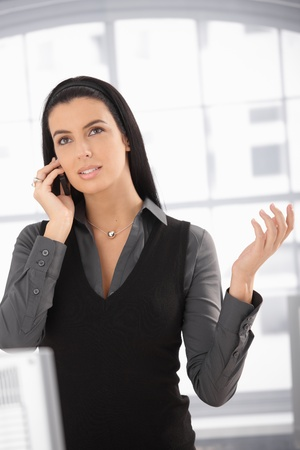 Attractive woman speaking on mobile phone, looking up, gesturing,
