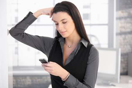 Smiling woman using mobile phone for texting, standing in office, thinking.