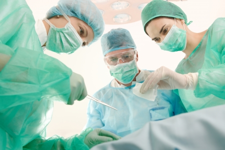 Surgeons and medical assistant wearing mask and uniform operating patient.