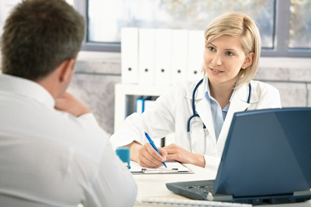 Doctor talking to patient in office, taking notes, smiling.