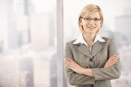 Portrait of smiling mid-adult businesswoman standing at skyscraper window.