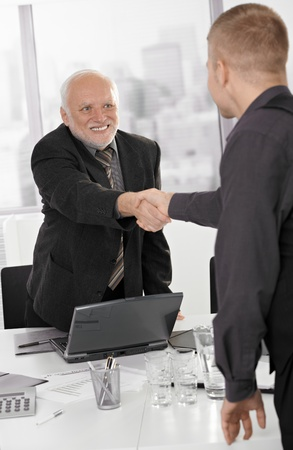 Senior executive shaking hands with businessman in office, smiling.の写真素材