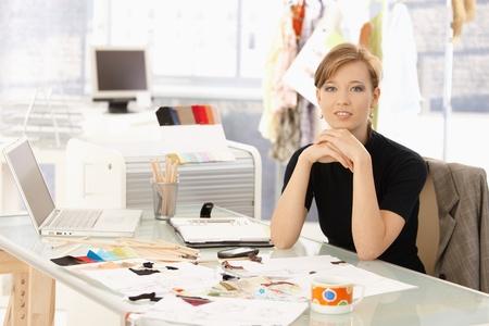 Portrait of attractive female fashion designer sitting at office desk, smiling.