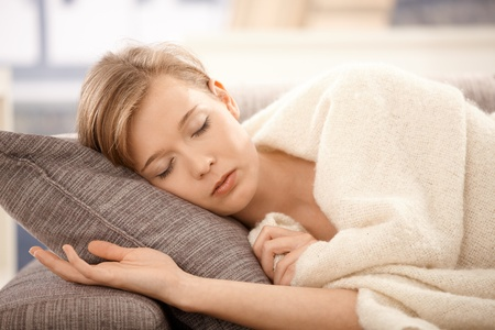 Young woman sleeping on sofa at home, covered with blanket.