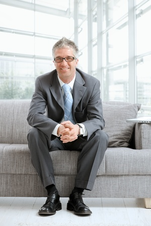 Happy gray haired businessman sitting on couch in office lobby, looking at camera, smiling.の写真素材