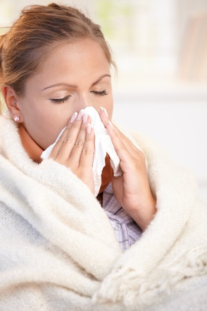 Young woman having flu, feeling bad, blowing her nose, wrapped up in blanket.
