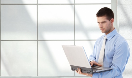 Young goodlooking man using laptop in office lobby, standing.