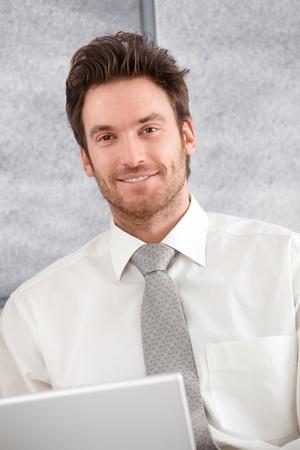 Photo pour Portrait of confident young businessman, smiling, using laptop. - image libre de droit