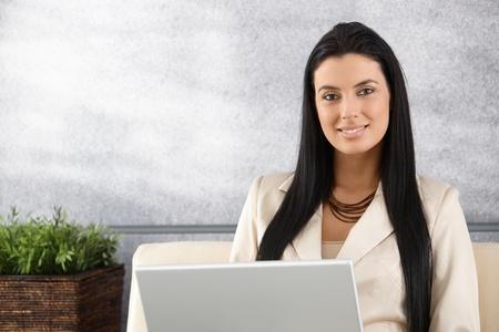 Photo pour Pretty young businesswoman working on laptop, smiling in elegant office. - image libre de droit