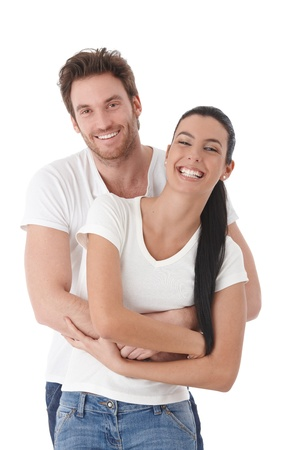 Happy couple standing over white background, laughing.