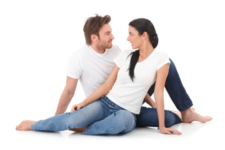 Romantic young couple sitting on floor, giving each other the eye, smiling