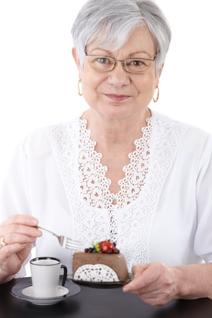 Portrait of senior woman eating chocolate mousse cake, smiling at camera.