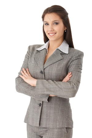 Pretty young businesswoman standing arms crossed, smiling, looking at camera.