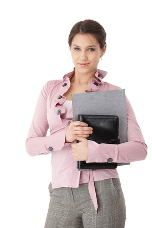 Pretty young secretary standing with folders in hands, smiling.