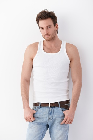 Goodlooking young man wearing undershirt and jeans, standing by wall.