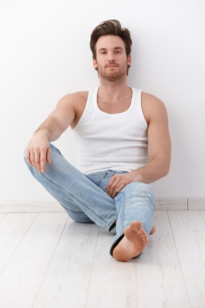 Handsome young man sitting on floor, leaning to wall, wearing undershirt and jeans.