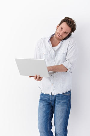 Busy young man using mobile and laptop, smiling.