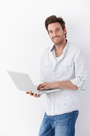 Handsome young man browsing internet on laptop, smiling.