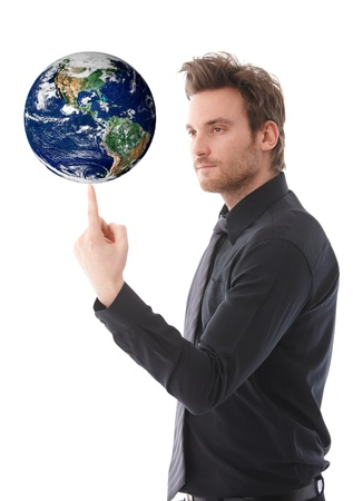 Goodlooking young businessman balancing a globe on his forefinger, concentrating.