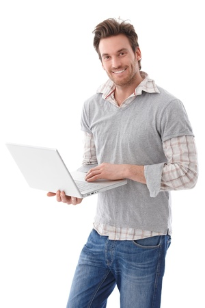Happy young man using laptop, standing, smiling.