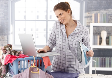 Multitasking woman at home, doing housework, ironing laundry and using laptop computer, talking on mobile phone, smiling.