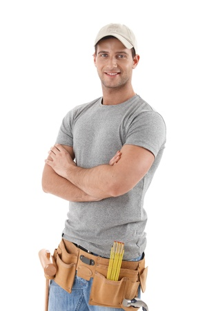 Handsome handyman in baseball hat standing with arms folded, smiling at camera, cutout on white.