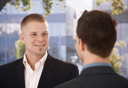 Photo pour Businessmen chatting outside of office, businessman smiling at colleague. - image libre de droit
