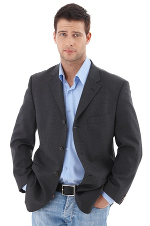Casual portrait of young charming businessman standing with hands in pocket, looking at camera, frowning.