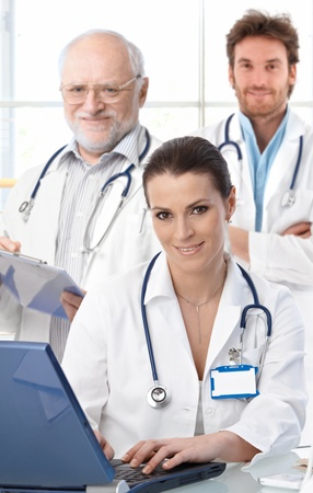 Doctors working at desk, female doctor in front, looking at camera, smiling.ᅵ