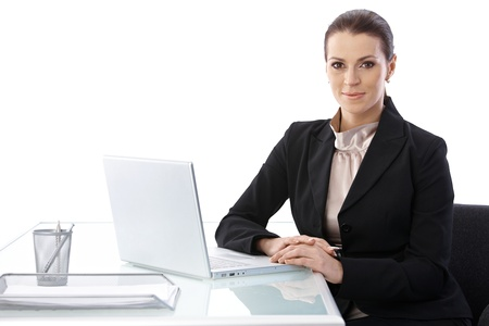 Cutout portrait of businesswoman sitting at desk with laptop computer, smiling at camera.