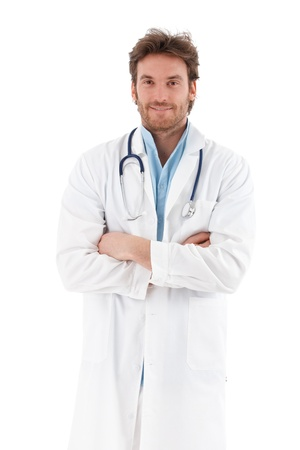 Handsome young doctor standing arms crossed, smiling at camera.